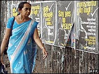 A woman walks past a poster on peace talks in Colombo, Sri Lanka