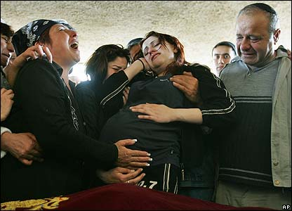 Irena Shaulov, mother of David Shaulov, holds the stomach of nine-month-pregnant daughter-in-law Radmila in the Israeli town of Holon, near Tel Aviv