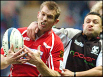 Scarlets skipper Dafydd James is dragged down by Ospreys wing Damian Karauna