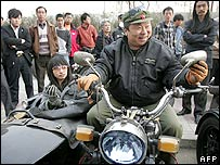 A biker adjusts his side mirror with a passenger in the side-car as people gather for the opening of Beijing Harley-Davidson's first authorized dealership in Beijing, 08 April 2006.