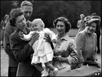 Princess Elizabeth helps her daughter Princess Anne stand on a wall, watched by King George VI, Queen Elizabeth, and Princess Margaret at Balmoral Castle, Scotland, in August 1951 