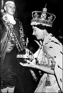 Queen Elizabeth 2, wearing the Imperial Crown, carries the symbols of authority, the orb and the and sceptre, as she leaves Westminster Abbey at the end of her coronation in June 1953