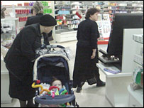 Orthodox women browse through the makeup counter