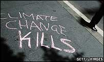 Pedestrian walks past graffiti which says 'climate change kills'
