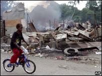 A boy cycles past the burnt-out remains of stores in Chinatown, Honiara