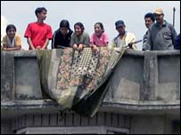 Kathmandu residents watch from a rooftop