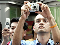Onlookers take pictures of a demonstration in Thailand