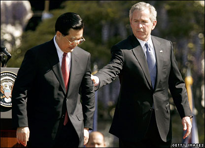 US President Bush (R) holds the arm of Chinese President Hu Jintao