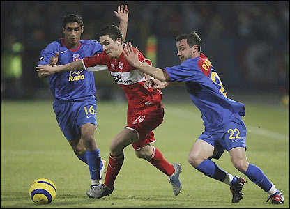 Stewart Downing attempts to force his way past Steaua's Banel Nicolita and Sorin Paraschiv