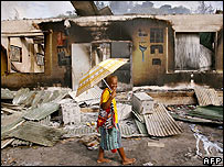Solomon Islander walks past a burnt out building in Honiara