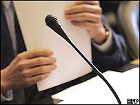 Delegate shuffling papers at meeting