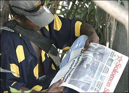 A man reads the Solomon Star newspaper with the headline PM Faces Motion of No Confidence in Honiara on Friday