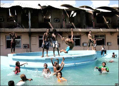 Children play in the pool of the burnt-down Casino Hotel in Honiara on Friday