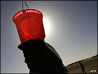 Refugee carrying a bucket of water on her head