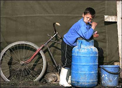 Romanian boy brushing teeth in tent camp