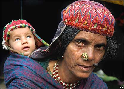 Zeba, a Kashmiri nomad, carrying her son