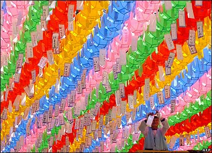 Worker attaches Buddhist name card to a host of colourful lotus lanterns