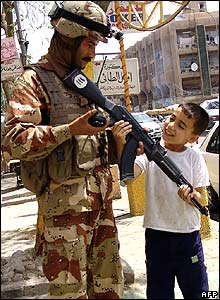 Boy looks at soldier's rifle in Baghdad