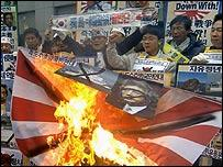South Korean protesters burn a Japanese military flag