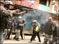 Policeman fires tear gas in the direction of protesters in Kathmandu