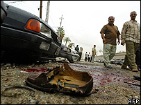 A ripped apart sandal lies in a pool of blood and debris after a mortar round exploded