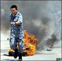 A policeman pulls away a burning tyre set alight by protesters