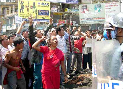 Protesters chant slogans in front of a line of riot police