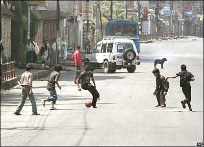 Children play football in a near deserted street in Kathmandu