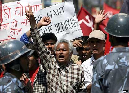 Opposition activists chant slogans in front of policemen in Kathmandu