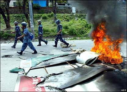 Police walk past burning tyres in Kathmandu