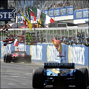 Michael Schumacher takes the chequered flag ahead of Fernando Alonso