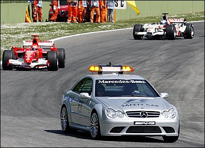 Michael Schumacher and Jenson Button follow the safety car