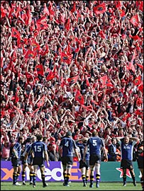 Munster fans celebrate as Leinster's dejected players wait for a conversion