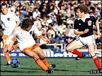 Scotland midfielder Asa Hartford takes on Johnny Rep