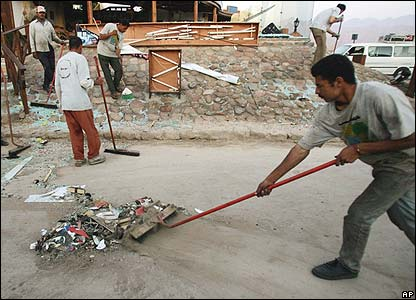 Workers clean up debris from the bomb attacks in Dahab
