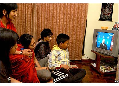A Nepalese family watches the king's TV address