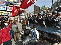 Nepalis wave flags at passing soldiers