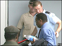 Charles Dausabea lawmaker, centre, arrives at Honiara Magistrates court on the Solomon Islands, Tuesday, April 25, 2006