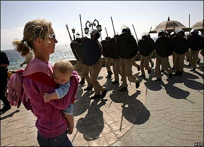 A mother carries her baby past Egyptian security forces