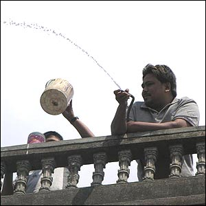 A local man sprays the crowds with water in Kathmandu on Tuesday (image: Daniel Sweeting)