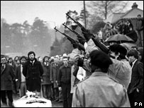 Three masked men fire volleys of rifle shots in 1981 over the coffin of hunger-striker Bobby Sands