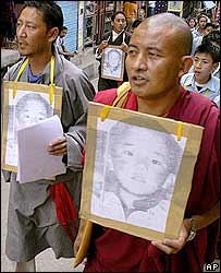 Tibetan monk walks along with others holding portraits of the 11th Panchen Lama, April 25, 2006.