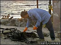 An Egyptian policeman collects the remains of a bomb in Dahab