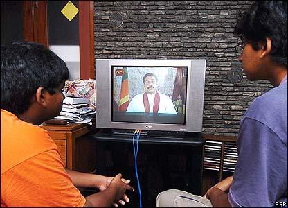 Sri Lankans watch the televised address of President Rajapakse