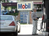 A customer looks at a gas pump where the prices have climbed over three dollars per gallon