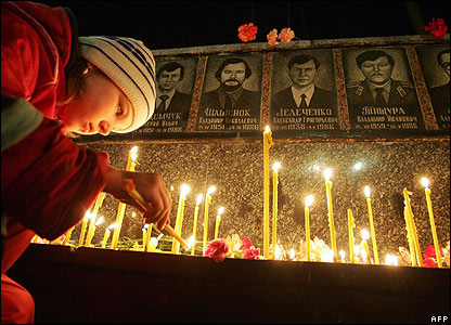A young girl lights a candle at the Chernobyl memorial in Slavutych