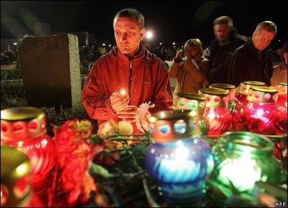 A man holds a candle at the Chernobyl memorial in Slavutych