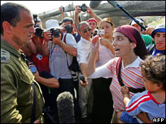 A woman settler argues with an Israeli soldier