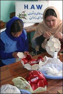 Women stitching footballs