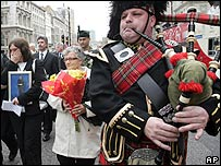 A lone piper leads the march to the Cenotaph